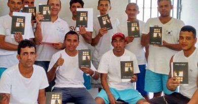 detentos segurando livros